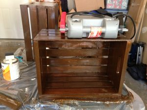 After gluing the wooden planks to the bottom of the crate, Chris put his heavy battery charger on top to make sure the glue dried properly.