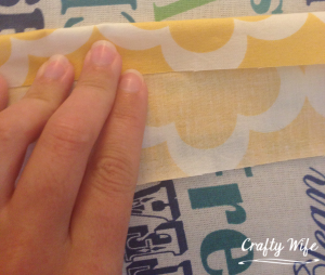 Once you've pressed the seam, open the fabric up and fold the sides into the pressed seam for the second time.  Press the seams down, then sew up the side.