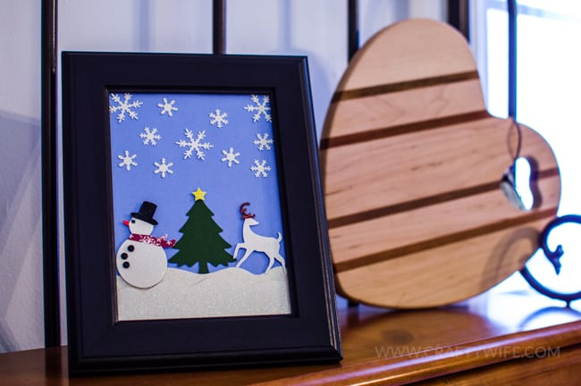 Use paper crafts to create a winter wonderland picture display for your home. Use a snowman hole punch and other paper craft items to create the scene.