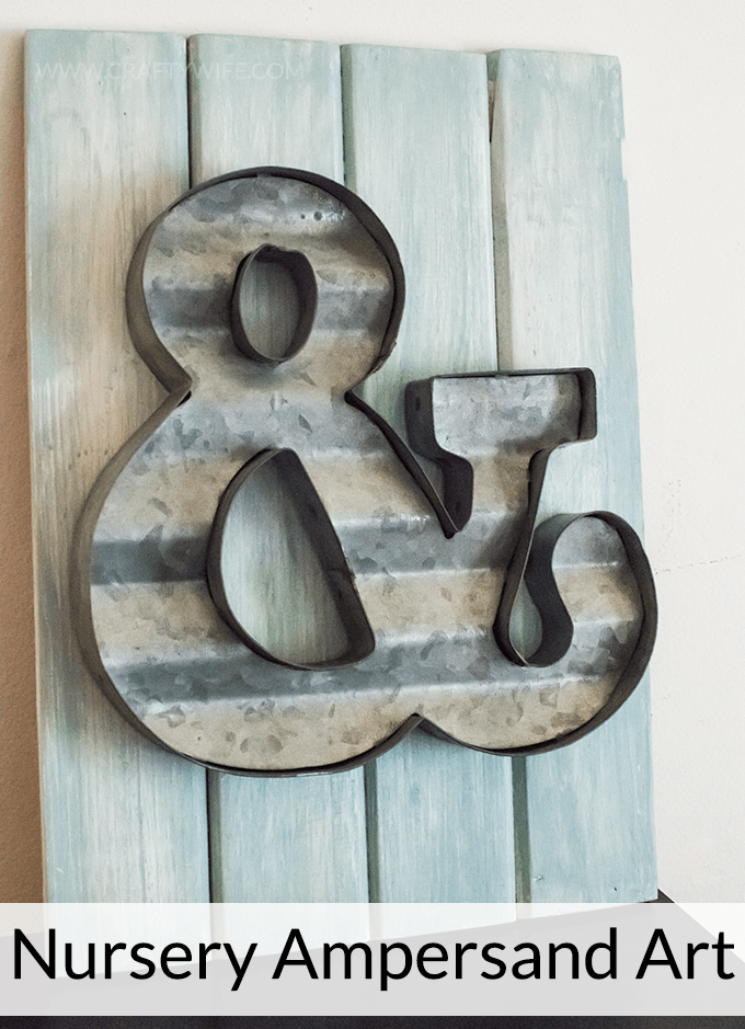 Create an easy art display with a metal ampersand and wooden board from Michaels Arts & Craft store. Perfect decor for a nursery or a gallery wall!
