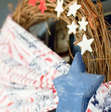 Welcome friends & family to your home all summer long with this simple Patriotic wreath! Made with stars & stripes fabric, wooden stars, & a grapevine base.